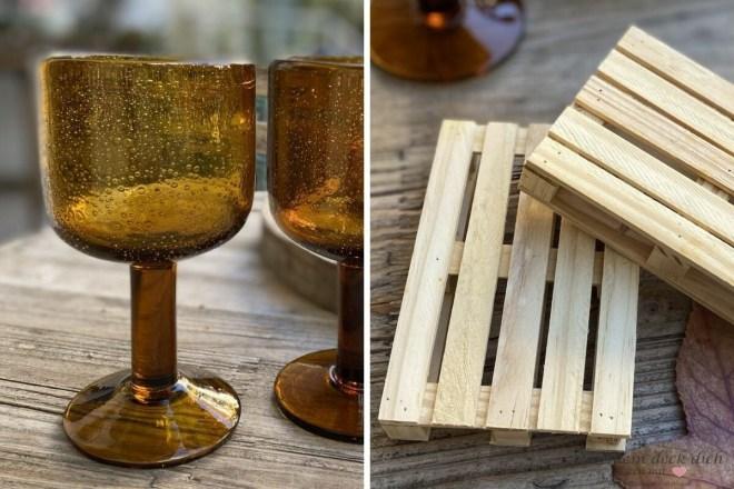 rustikale Weingläser und kleine Holzpaletten