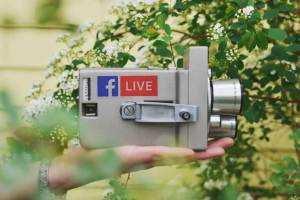 Image of a hand holding up an old video camera with the label Facebook LIVE on it.