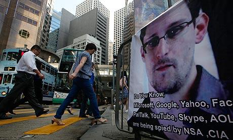 Les gens passent devant une banderole soutenant Edouard Snowden dans le quartier des affaires de Hong Kong. Photo: Kin Cheung / AP