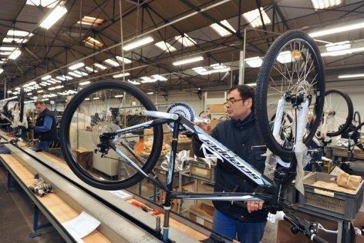 Un travailleur vérifie un vélo sur la ligne d'assemblage dans l'usine de Cycleurope à Machecoul, ouest de la France le 7 Mars.