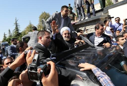 Le président iranien Hassan Rouhani salue les supporters comme son cortège tire hors de l'aéroport Mehrabad de Téhéran à son arrivée à New York, le 28 Septembre 2013