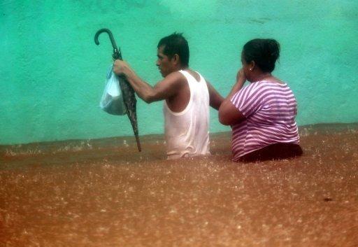 Un couple patauge dans une rue inondée à Acapulco, l'État de Guerrero, au Mexique, le 15 Septembre 2013.