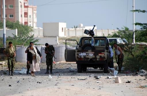 Les forces de sécurité yéménites sont vus le long d'une route principale jonchée de débris après un kamikaze a fait exploser un véhicule à l'extérieur d'un palais présidentiel à Mukalla le Février 25, 2012