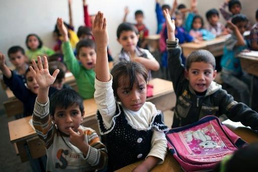 Enfants syriens participent à une classe d'une école dans le quartier Masai Hanano de la ville du nord d'Alep, le 23 Septembre 2013