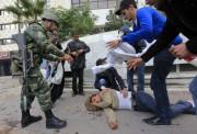 Un soldat tunisien et des manifestants apportent aide à un manifestant