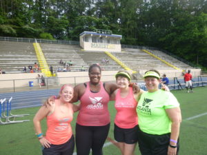 4 women in running clothes at track meet