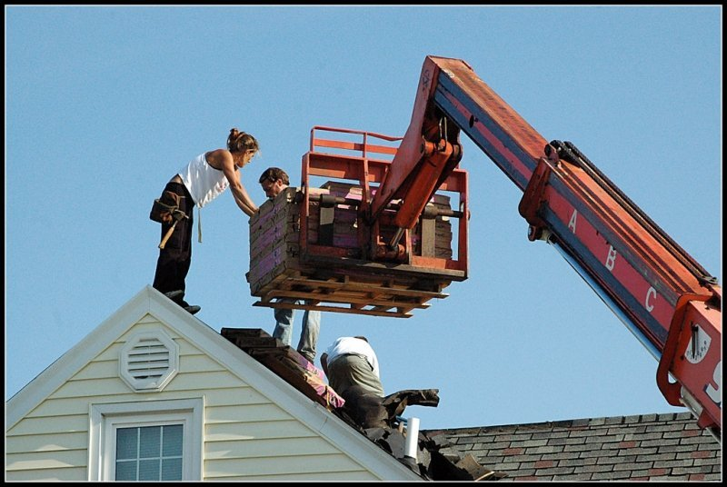 Roofing crew using a crane to transfer shingles to the work area.