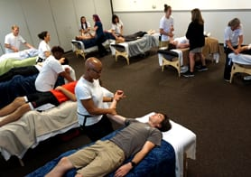 overview of a classroom filled with massage therapy students practicing massage techniques at The Lauterstein-Conway Massage School & Clinic during their massage therapy program