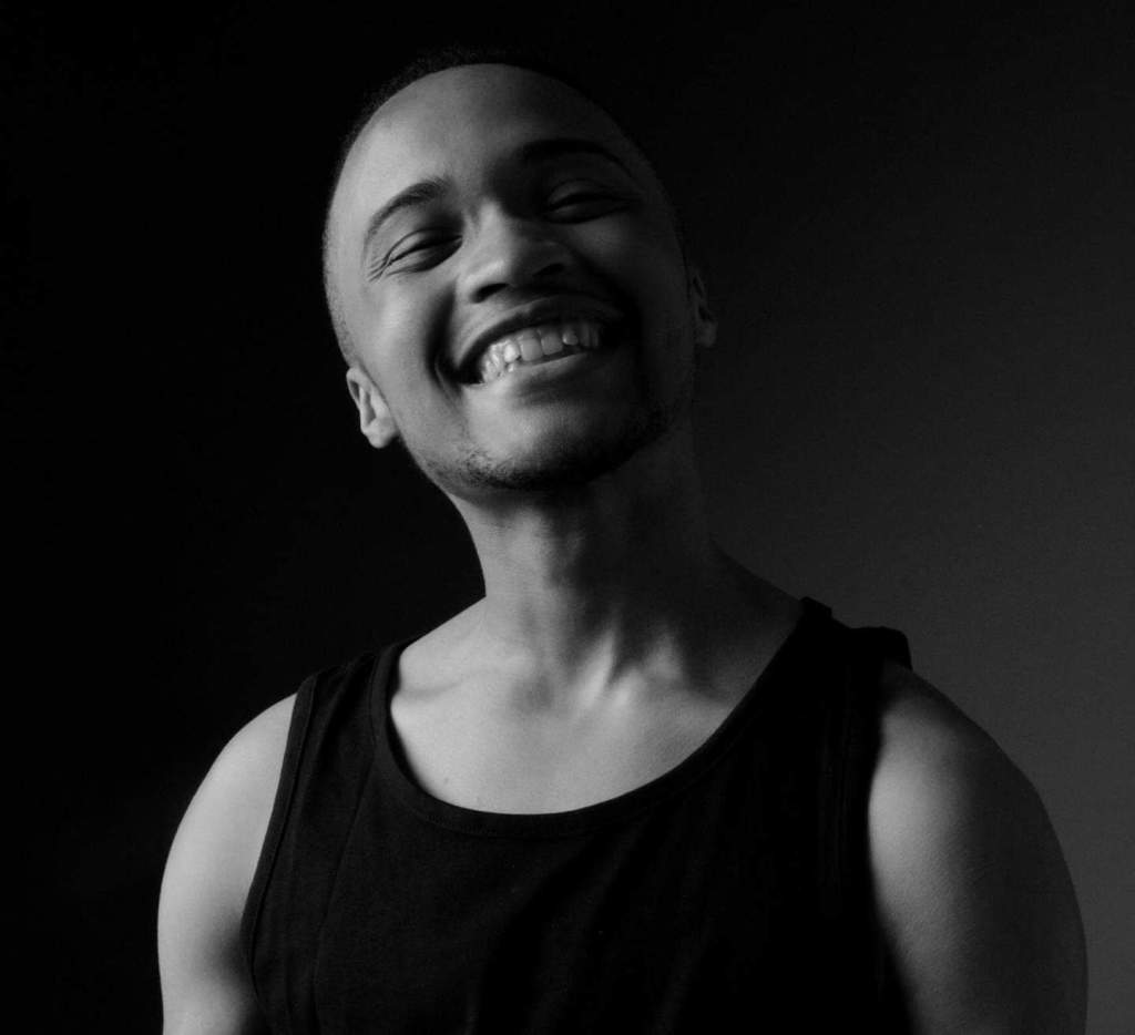 Cydney wears a dark colored tank top and smiles widely, radiating joy in a black and white photo.