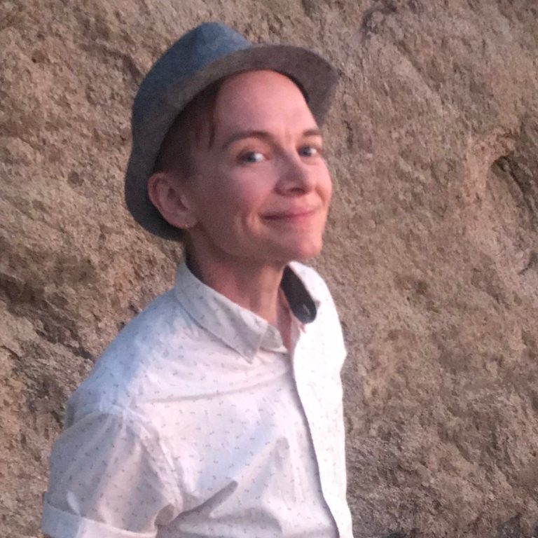 Sid smiles and poses slightly to the side, standing in front of a brown rock wall, wearing a light grey fedora and a white button up shirt.