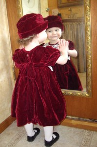 Little Girl Admiring Herself in the Mirror