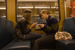 Girls sharing headphones