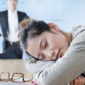 Young businesswoman sleeping during meeting, disappointed Boss looking at her