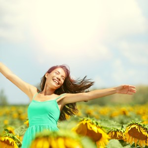 Happy woman in sunflower field. Summer girl in flower field cheerful and joyful. Multiracial Asian Caucasian young woman dancing, smiling elated and serene with arms raised up.