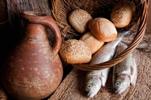 Wine loaves of bread and fresh fish in an old basket