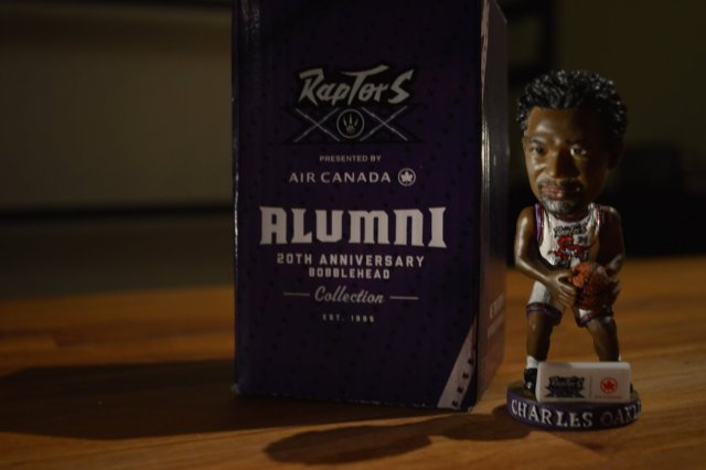A Charles Oakley bobblehead situated next to its box.