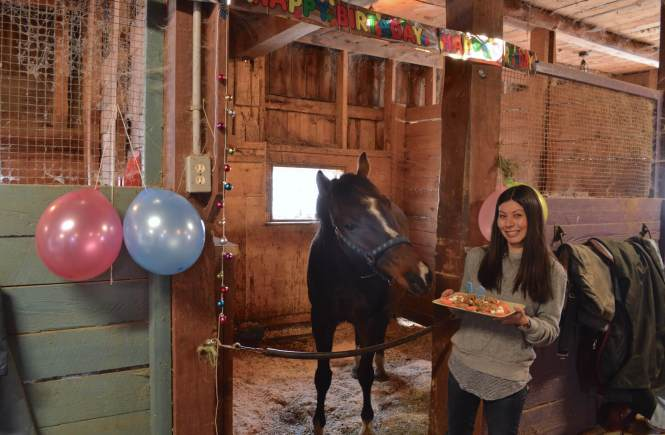 Meg standing next to Griffin presenting him with his platter of horse treats.