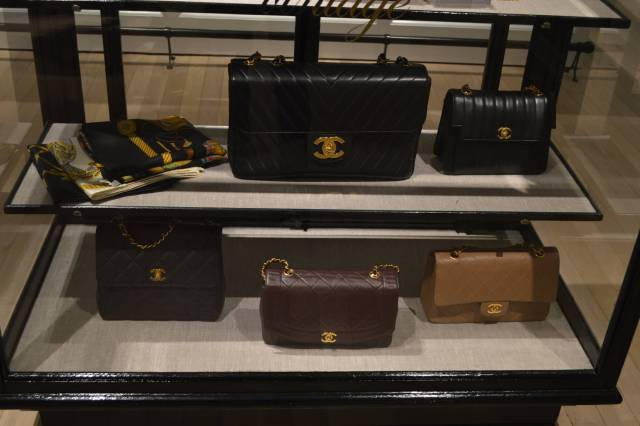 A showcase displaying various vintage Chanel handbags.