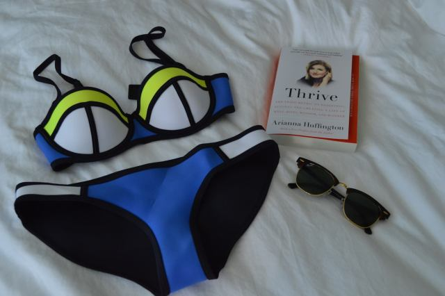 Showing what you should bring to Nordik Nature spa which includes a bathing suit, a book and a pair of sunglasses.