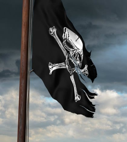 Tattered pirate flag flying high on a windy day