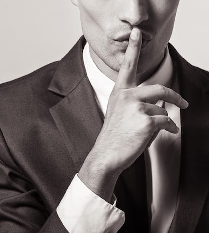 Portrait of a young businessman with finger on his lips