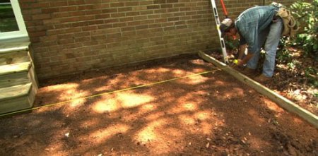 How to Lay a Paver Patio   Today s Homeowner Installing treated wood border around paver patio