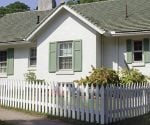 Summer sun shining on house with white picket fence.