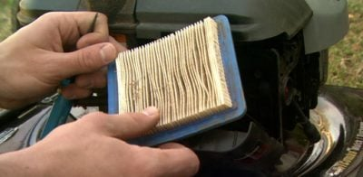 Changing the air filter on a lawn mower.