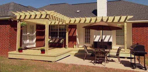Completed wood pergola shade arbor on back of  brick house.