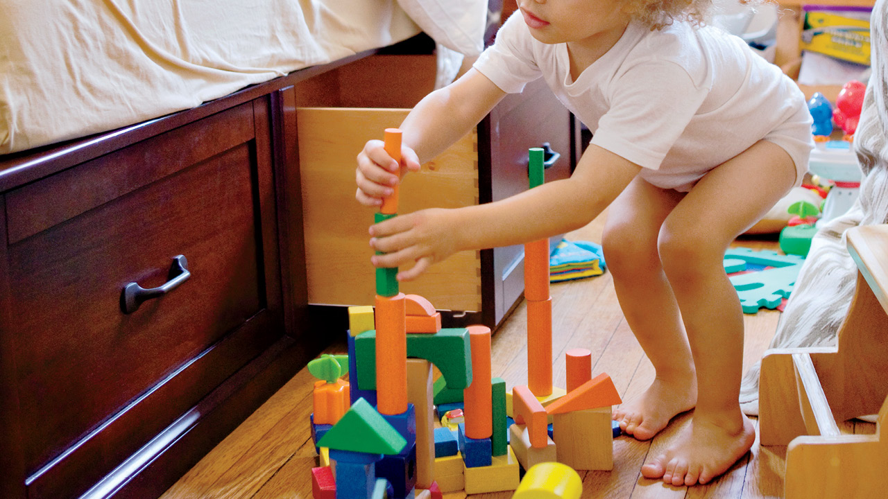 a toddler out of their bed playing with blocks for a story on milestone development