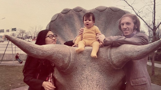 A retro photograph of two parents with their baby sitting on a statue of a triceratops