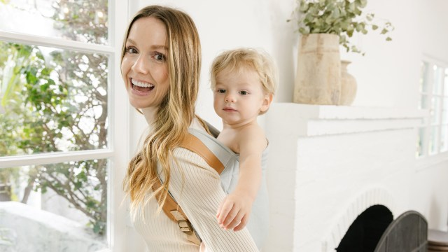 A photo of a parent in a white shift and blond hair, wearing a baby carrier on their back. Their baby is inside the carrier. They are in a white room with a window.