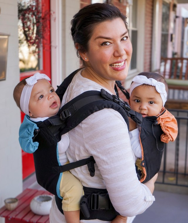 A photo of a parent in a white and pink striped top wearing a twin baby carrier. They have one baby on their chest and another on their back. Both babies are wearing bow headbands.