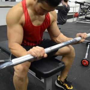 Hombre entrenando antebrazo con barra en gym