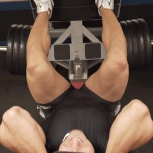 Hombre haciendo prensa en gimnasio