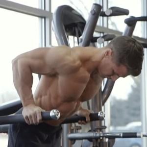 Hombre trabajando tríceps en paralelas (gym)