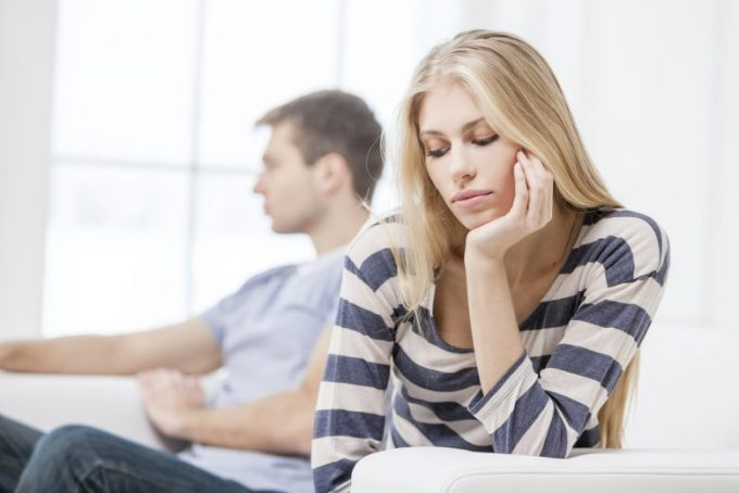 Upset young woman sitting with her husband in the background