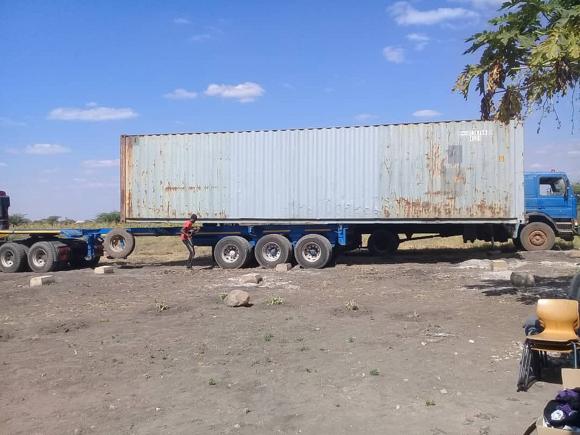 Herunterladen des Containers vom Transport-LKW mit Hilfe eines Kranwagens