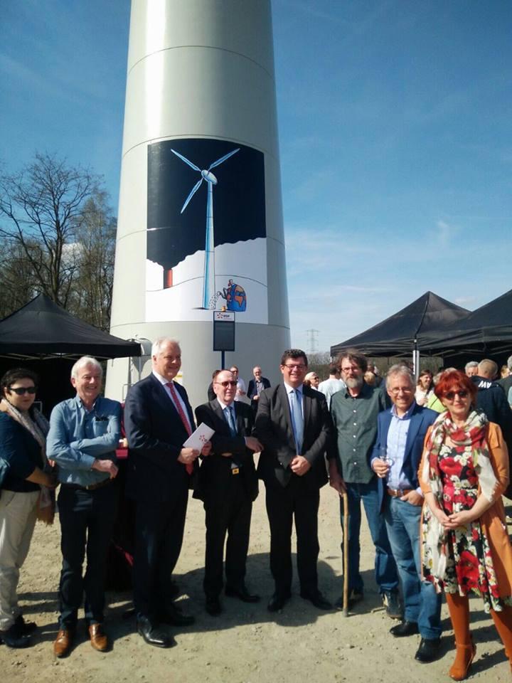 Minister Tommelein poseert samen met andere mensen voor windmolen