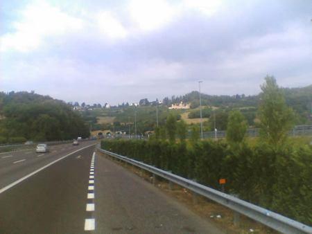 Corridoio viario vicentino (sette corsie per ciascun senso di marcia, doppio spartitraffico e franchi vari) in direzione Milano: sullo sfondo i fori delle prime quattro gallerie di attraversamento dei Berici (secondo il primo progetto, a sx del tratto, dovrebbe affiancarsi la nuova ferrovia Av)