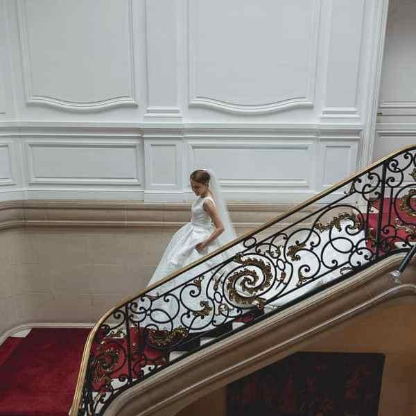 La mariée descend les escaliers avec sa robe de mariage