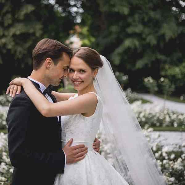 Photos de couple des Mariés dans le jardin avec des roses blanches