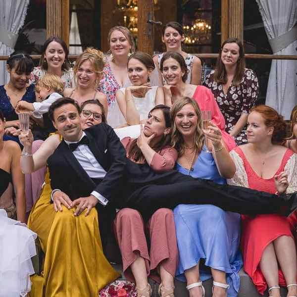 Photo de groupe pendant un mariage le marié s'allonge sur les filles