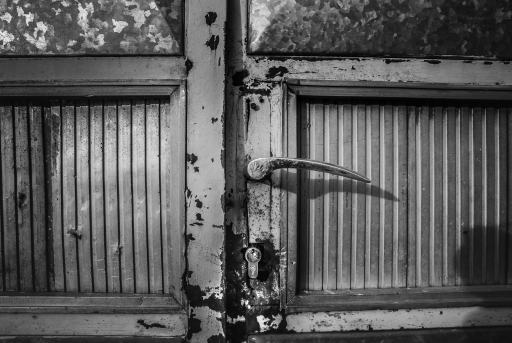Close up photograph of a door and door handle.  Photograph converted to black and white for graphic effect.