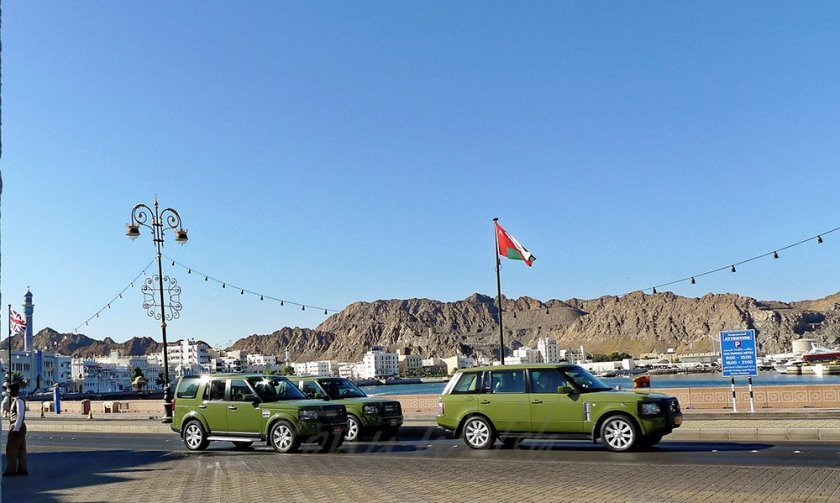 Queen Elizabeth waves from front Range Rover on way to the Palace in Muscat