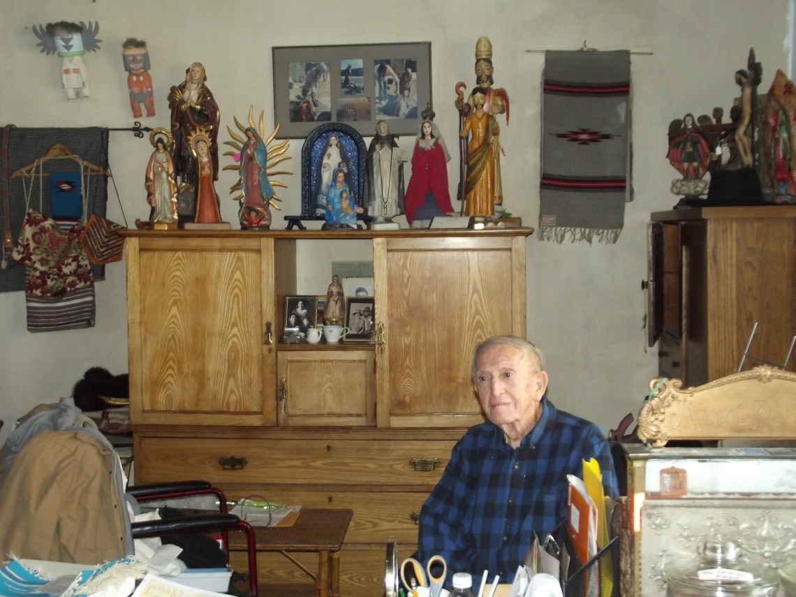 Elderly man seated in a shop selling antiques and crafts