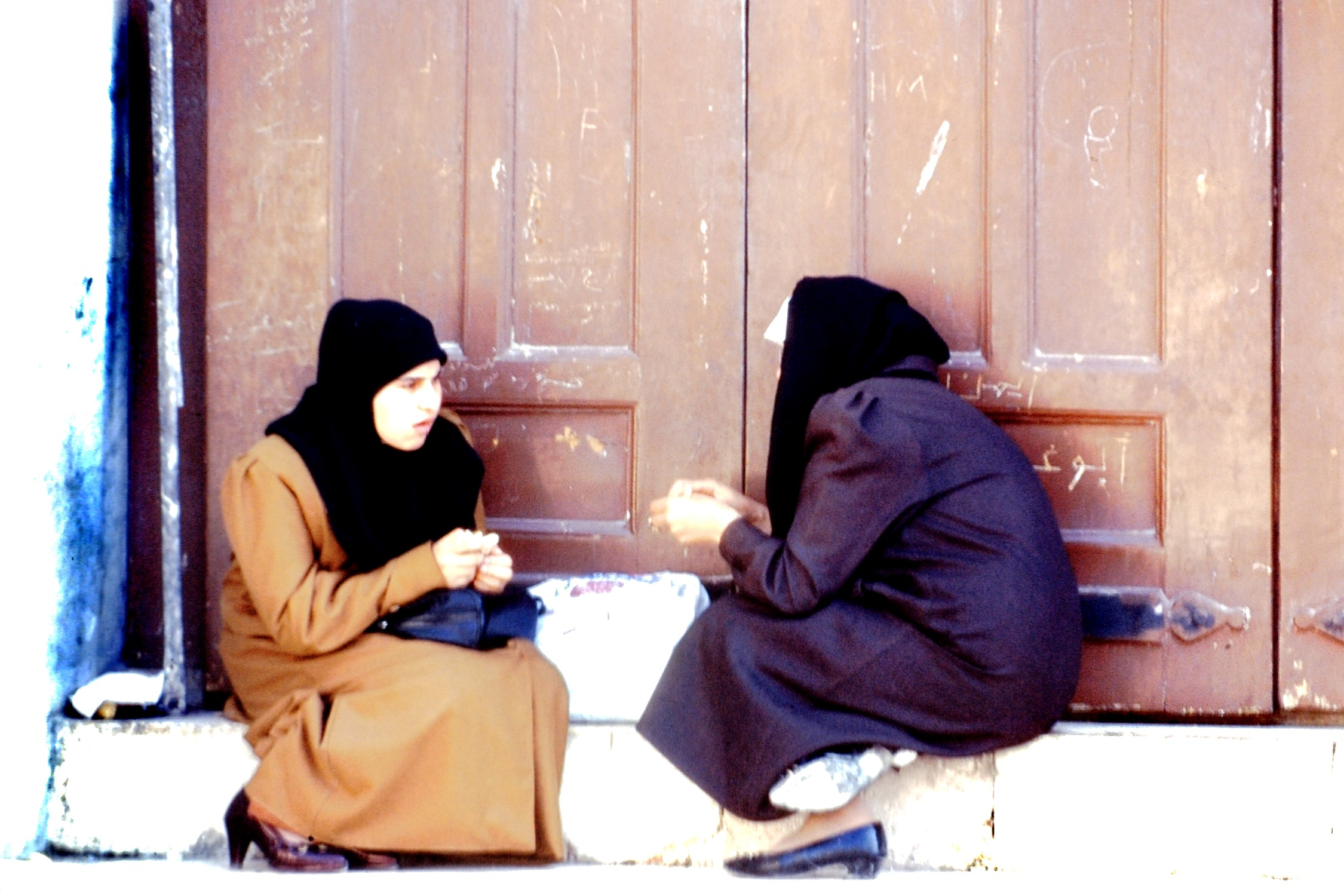 Two women sitting on a doorstep