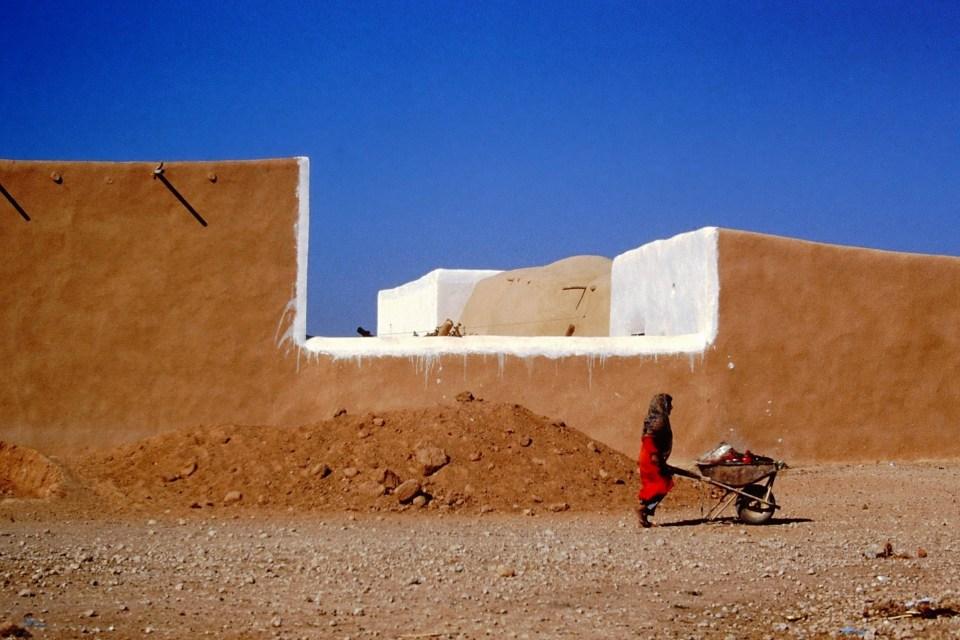 Adobe walls, woman pushing a wheelbarrow