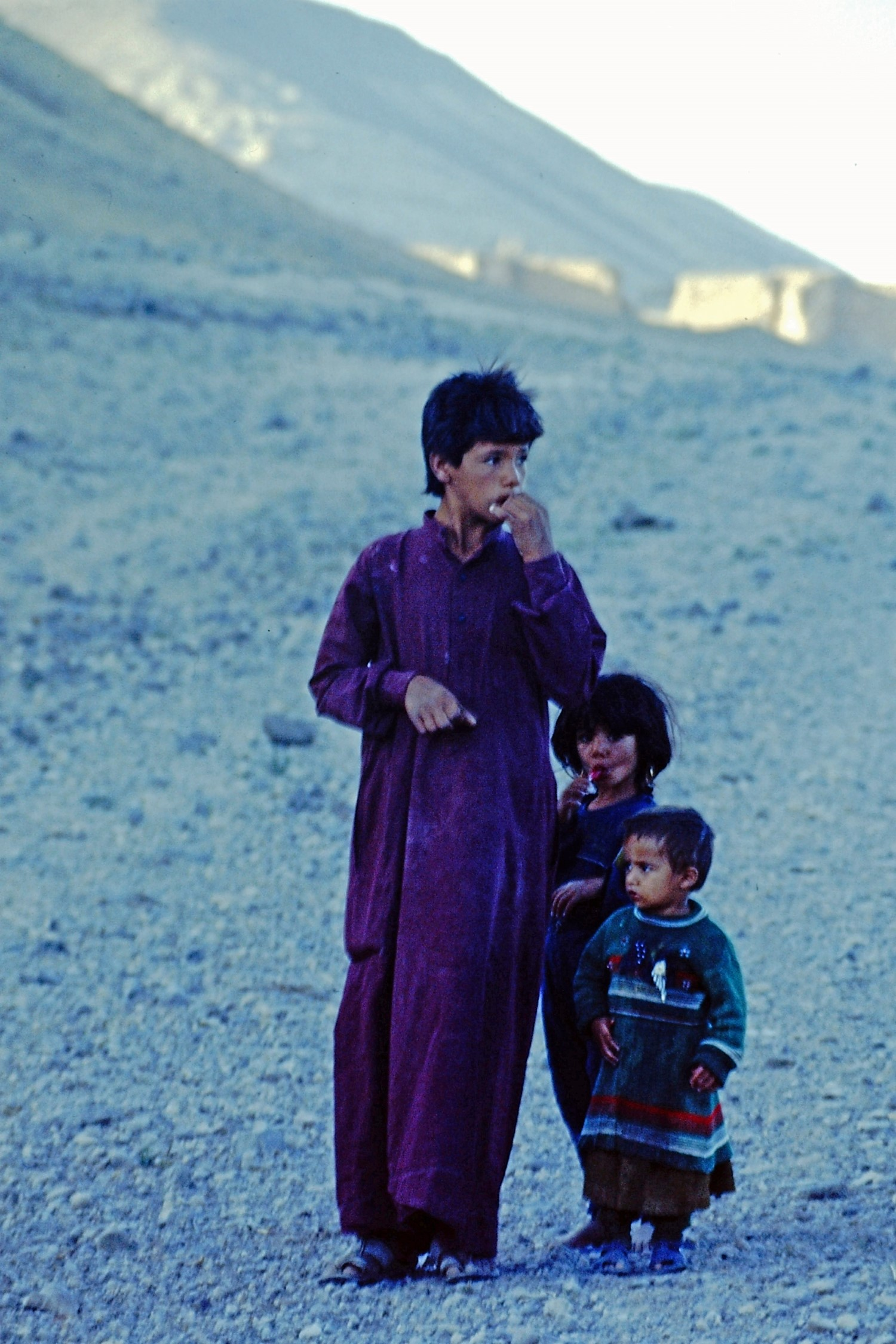 Three children in a stony desert