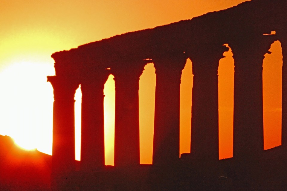 Sunrise with ruined columns silhouetted